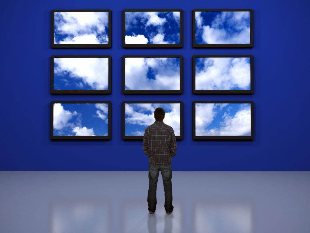 man standing in front of several video tv screens